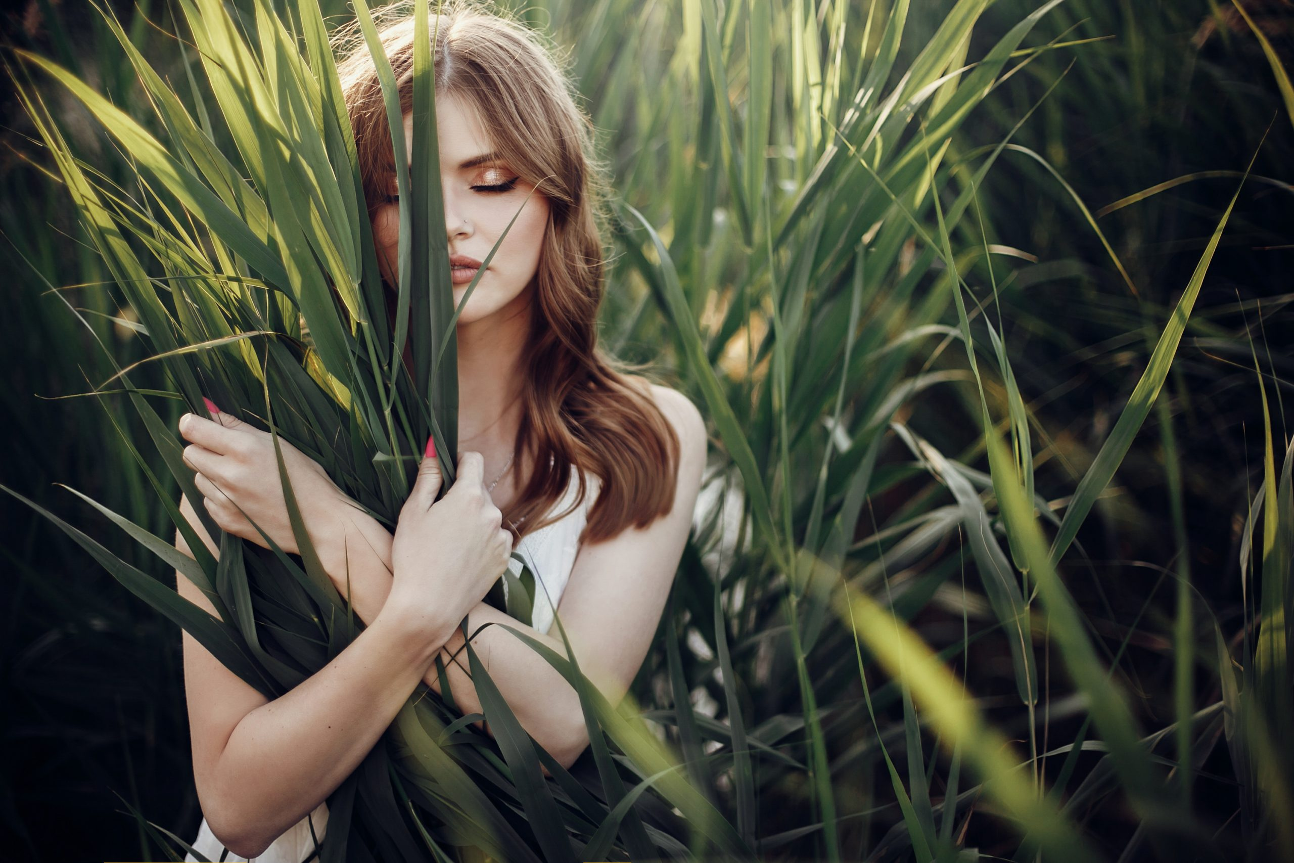 beautiful boho girl posing in grass at sunset light near lake. attractive sensual young woman embracing in cane near beach. summer vacation. save environment concept